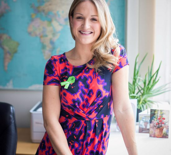 A smiled woman standing in an office