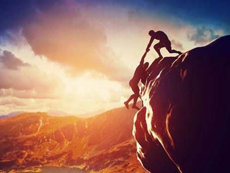 Men climbing up in high mountains and helping each other