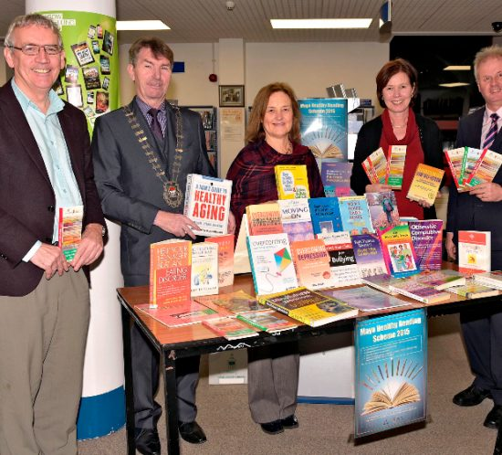 A group of people presenting books, and standing behind a table covered with a large amount of various books.